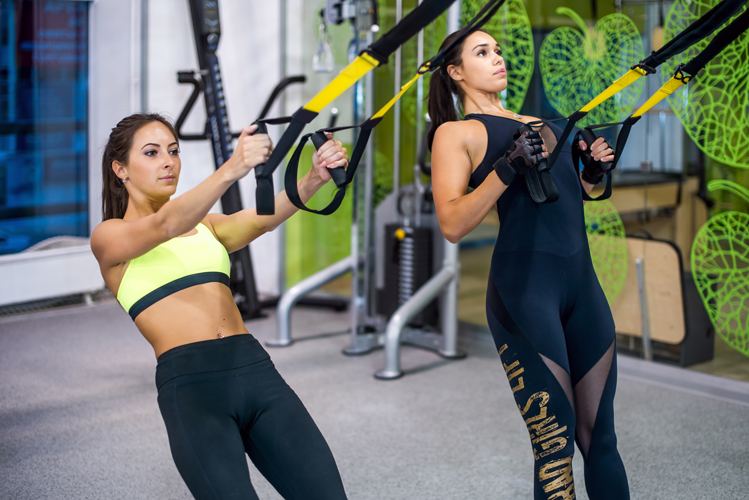 woman-exercising-with-suspension-straps-in-fitness-club-or-gym